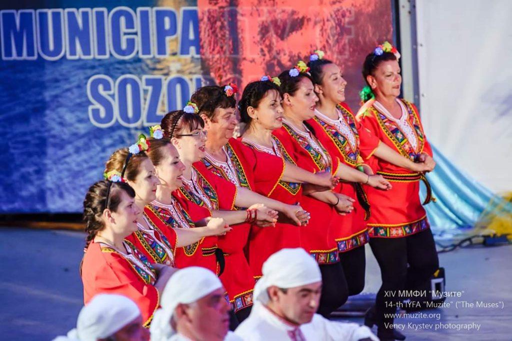 """Група за народни хора """"Средногорци"""" танцува на сцена в червени туники"""