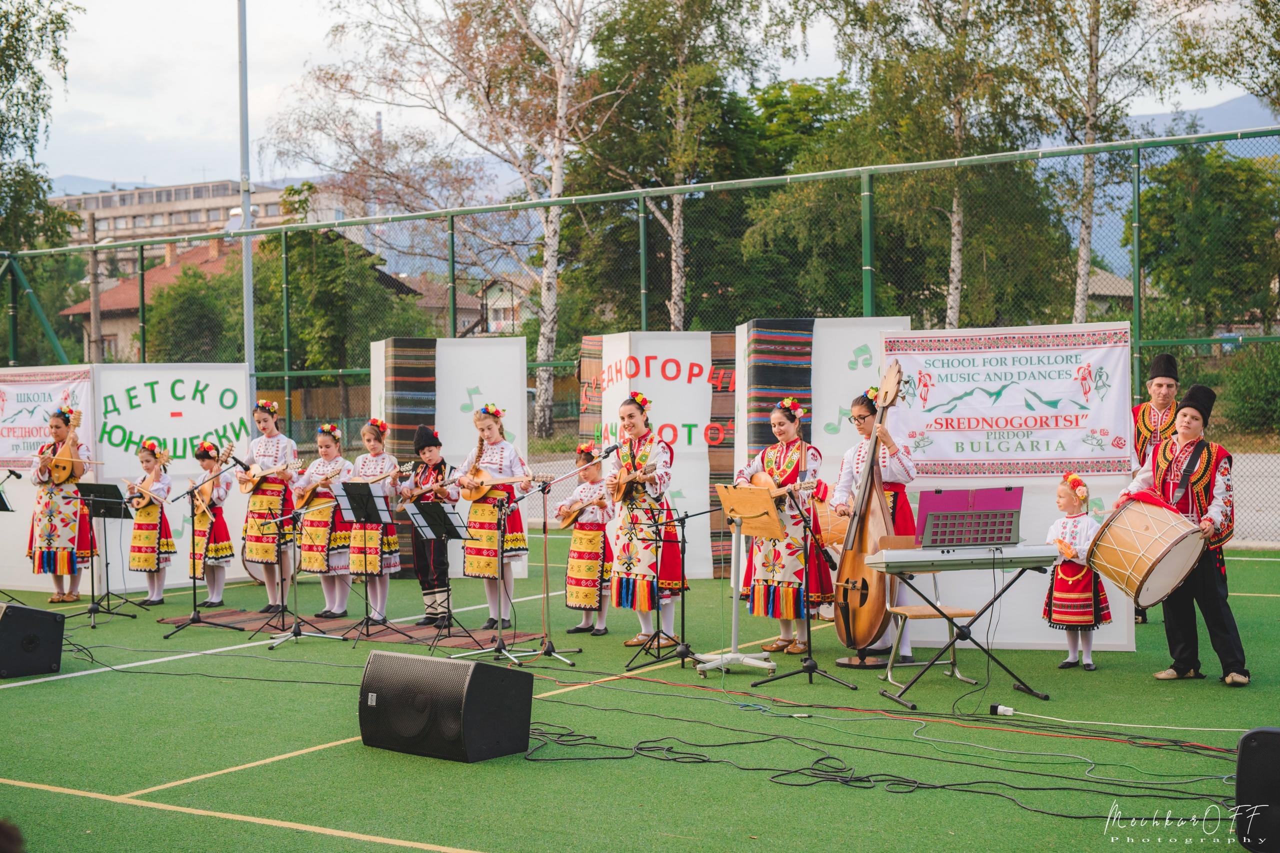 Деца, облечени в носии свирят на народни инструменти